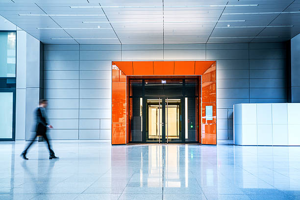 blurred businessmen walking inside a modern building - entrance stock photos and pictures