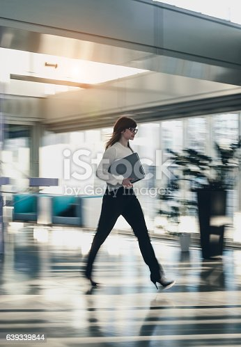 Businesswoman Walking Through Office Corridor and Carrying a Laptop