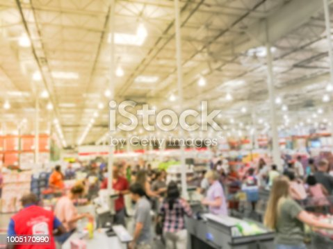 Wholesale shopping, sale, payment, consumerism and people concept. Blurred image cashier with long line of customer with clerk support at check-out counter of warehouse store in America