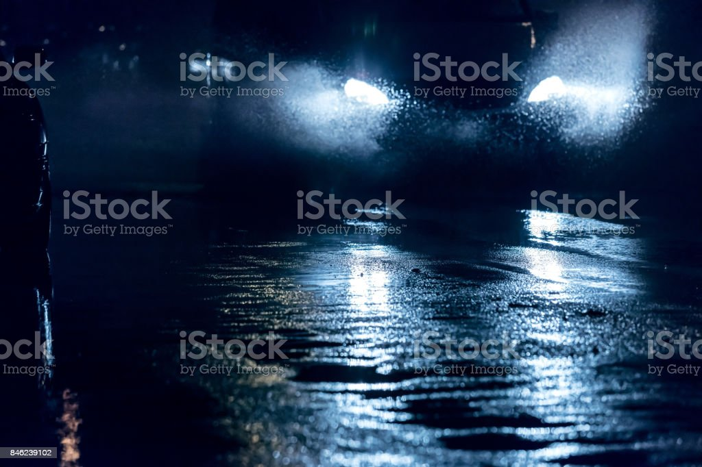blurred view of car headlights reflecting on wet asphalt during rainy...