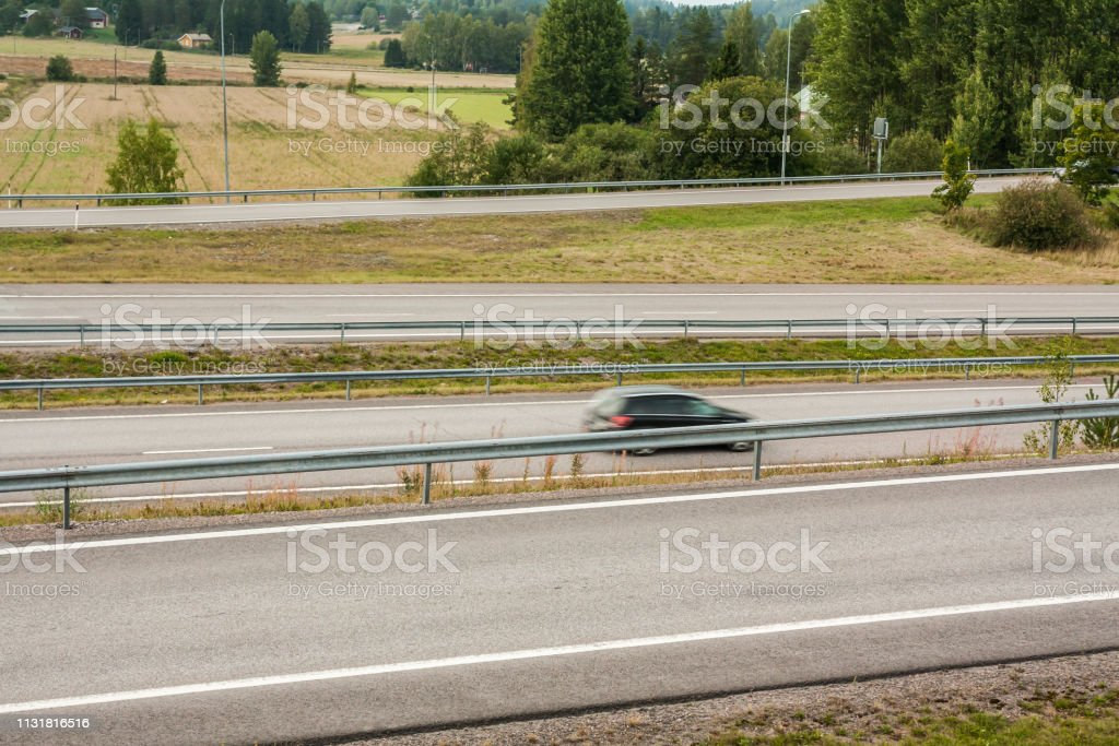 Blurred car in motion. Asphalt roads with car at autumn in Finland.