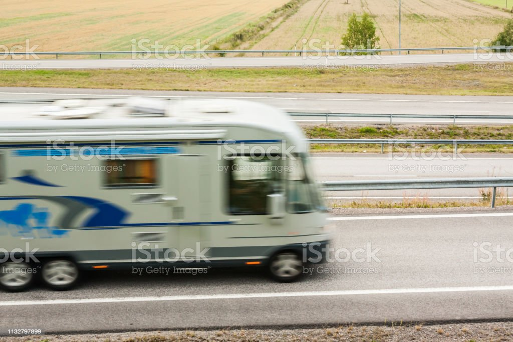 Blurred caravan car in motion. Asphalt roads with car at autumn in...