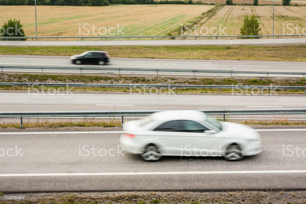 Blurred cars in motion. Asphalt roads with cars at autumn in Finland.