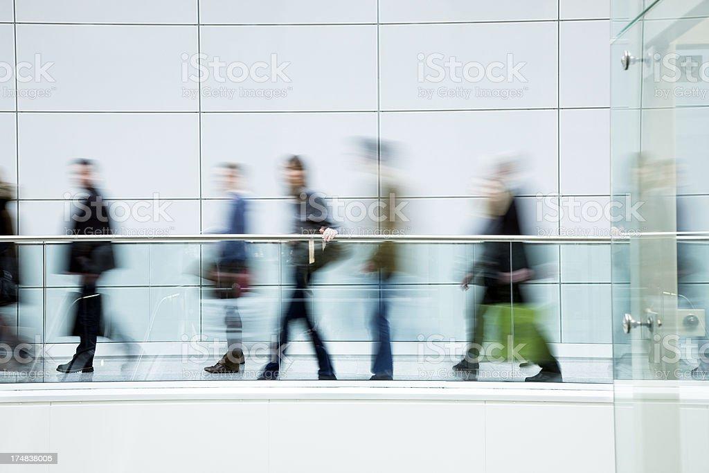 Blurred Casual People Walking Along Elevated Walkway Indoors royalty-free stock photo