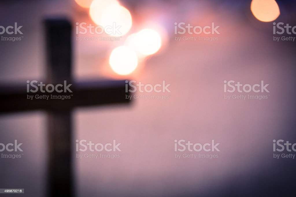 A background of bokeh lights with a soft, out of focus, wooden cross.