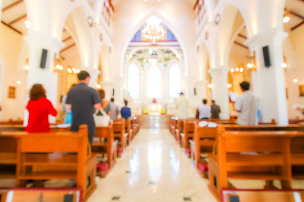 blurred christian mass praying inside the church blurred christian mass praying inside the church place of worship stock pictures, royalty-free photos & images