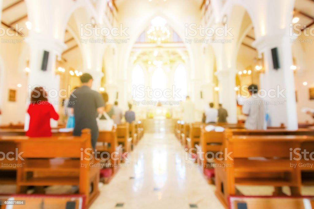 blurred christian mass praying inside the church stock photo