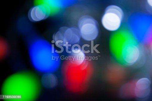 693852952 istock photo Blurred christmas lights dark blue, white, red, pink, green background. Abstract bokeh with soft light. Shiny festive texture 1193539285