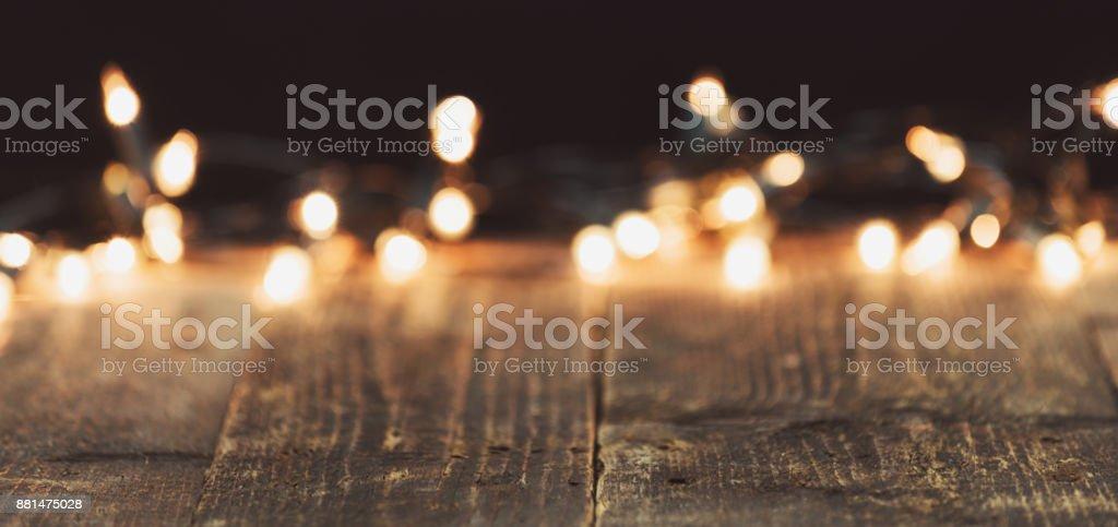 Weihnachtsbeleuchtung auf rustikalen Holztisch verwischt. Stimmungsvolle Weihnachten Hintergrund mit Exemplar – Foto