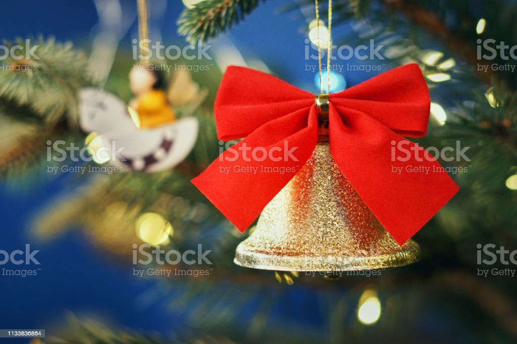 Blurred Christmas picture. Bright golden bell with a velvet red bow...