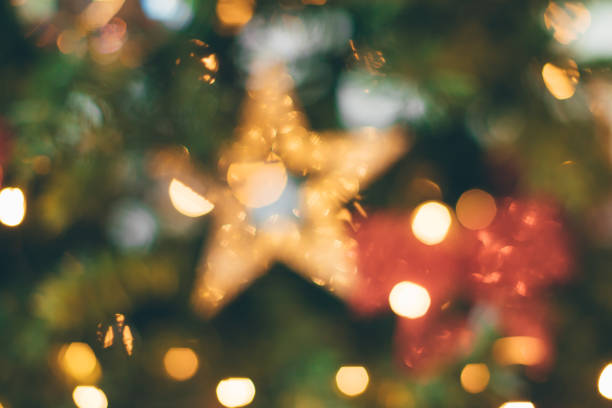 Blurred Christmas tree, lights decorations and a gold star, background