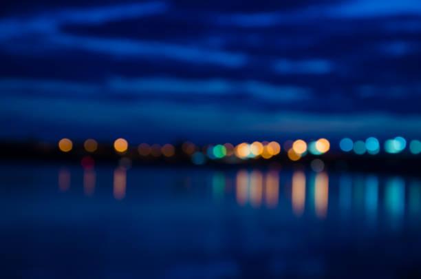 Lumières de la ville floue avec effet bokeh reflétée sur l'eau - Photo