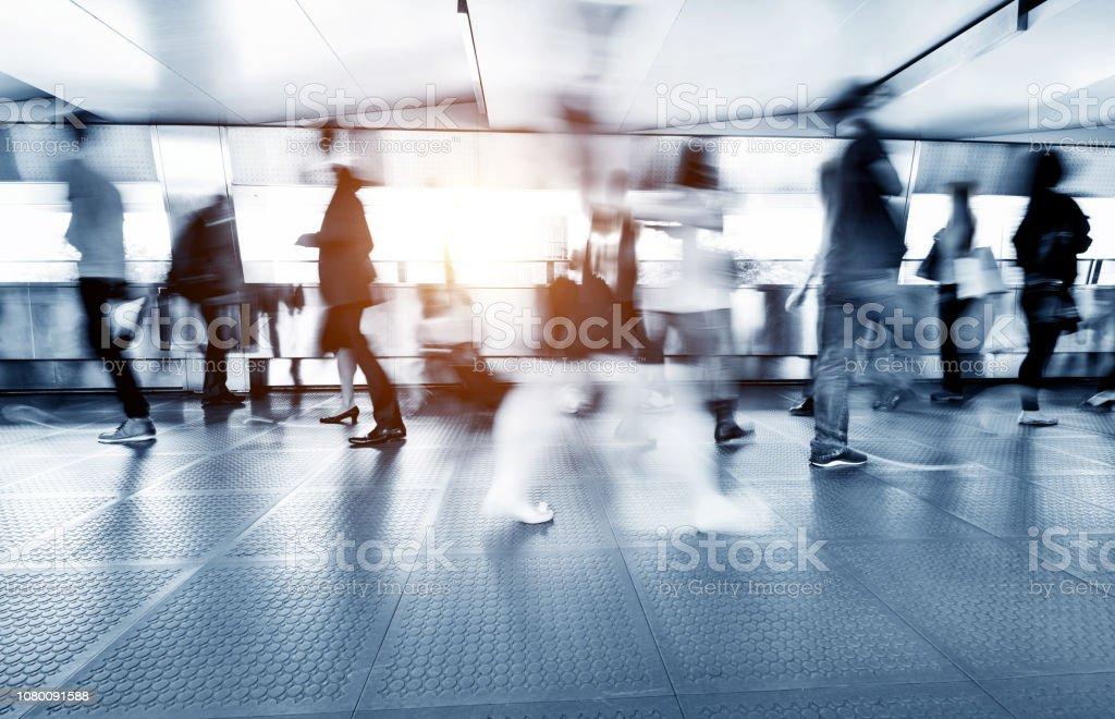 Blurred commuters walking on footbridge stock photo