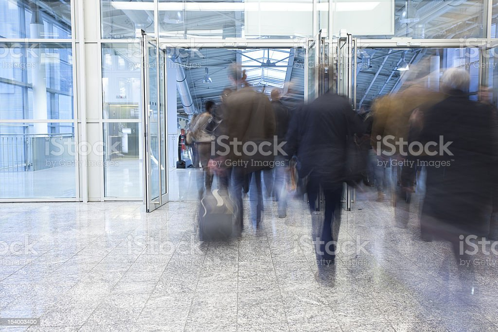 Blurred Commuters Walking Through Glass Doors royalty-free stock photo