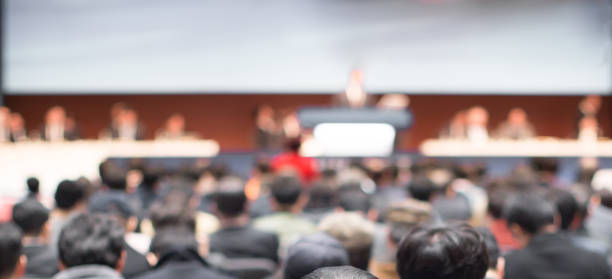 Blurred conference with panel speakers on stage during debate. Presenters at corporate seminar talking to audience.  Defocused business leadership CEO lecture. Executive board of directors. - foto stock