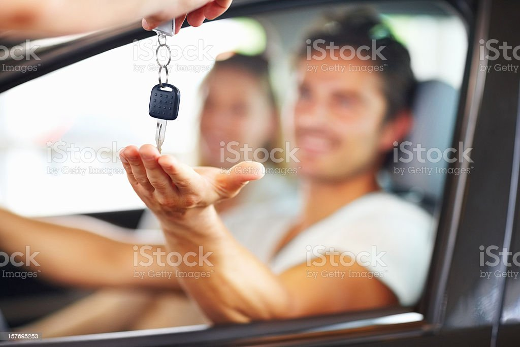 Blurred couple with man receiving car key from salesman royalty-free stock photo