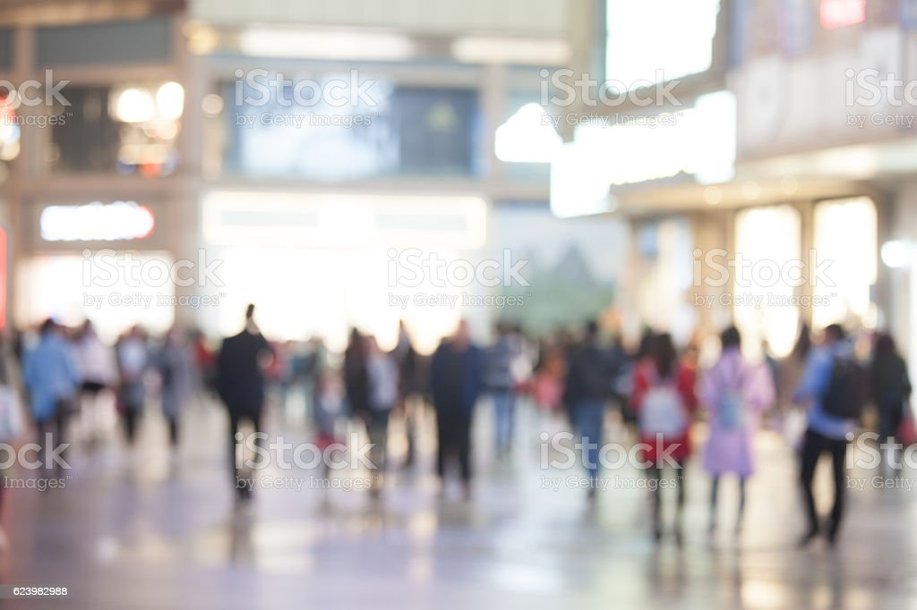 Blurred crowd in busy and brightly-lit shopping street at night stock photo