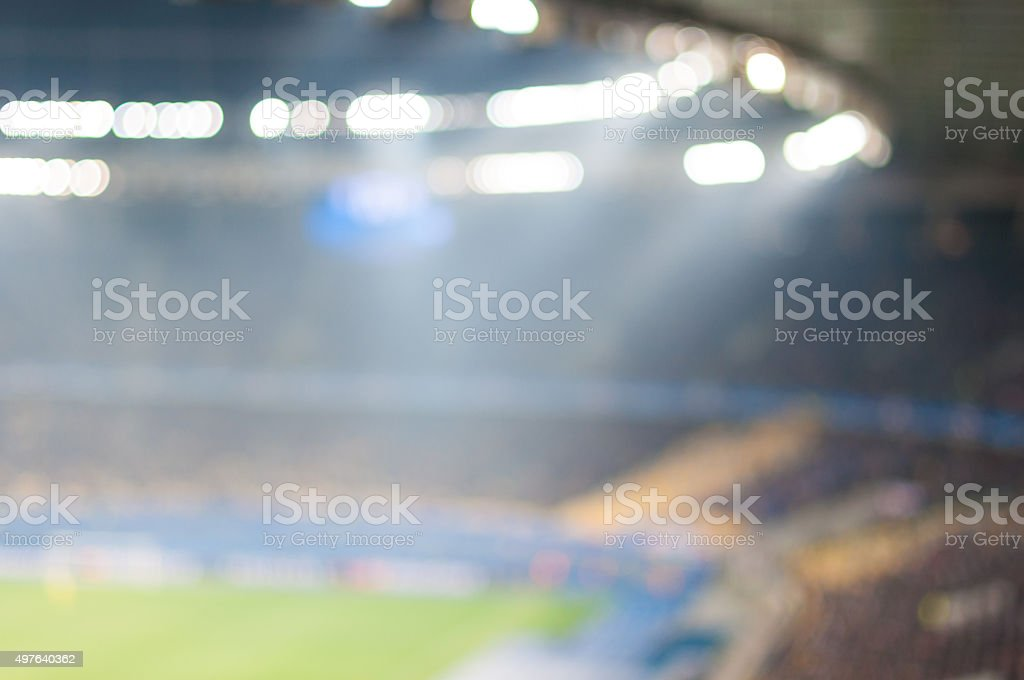 Blurred crowded football stadium with field, stands and spectators. 2016 stock photo