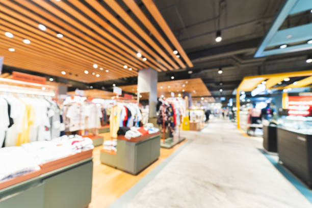 blurred, defocused background of clothing shops in modern shopping mall or department store. shopaholic lifestyle, or fashion dress outlet business concept - household equipment stock pictures, royalty-free photos & images