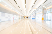 Blurred, defocused bokeh background of exhibition hall or convention center hallway. Business trade show event, modern interior architecture, or commercial tradeshow conference seminar concept