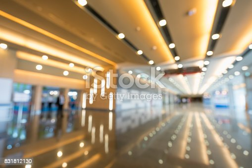 istock Blurred, defocused bokeh background of grand hallway, exhibition hall, or trade show event. International convention center, modern interior architecture, or commercial tradeshow organizer concept 831812130