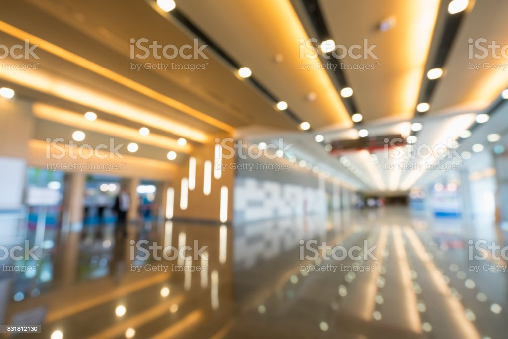 Blurred, defocused bokeh background of grand hallway, exhibition hall, or trade show event. International convention center, modern interior architecture, or commercial tradeshow organizer concept stock photo