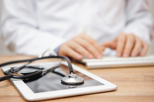 istock Blurred doctor in background typing on computer keyboard with tablet 520834322