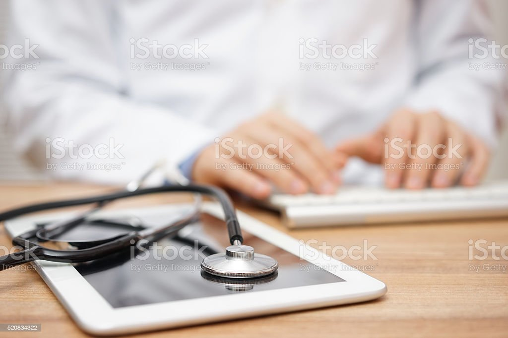 Blurred doctor in background typing on computer keyboard with tablet stock photo