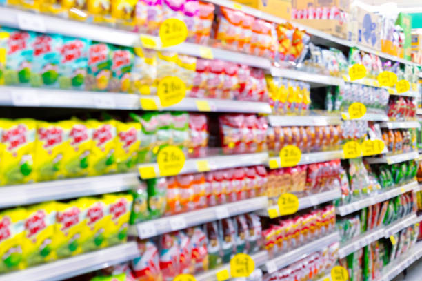 Blurred fast food snacks for sale on supermarket shelf. Blurred fast food snacks for sale on a supermarket shelf. A picture with grain and color from film simulation filter. snack aisle stock pictures, royalty-free photos & images