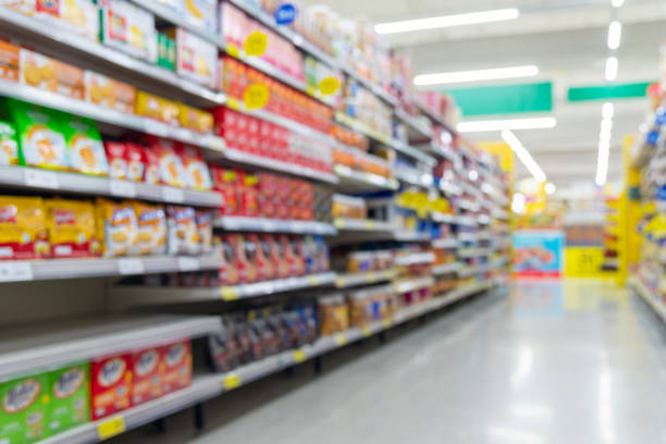 Blurred fast food snacks for sale on supermarket shelf. Blurred fast food snacks for sale on a supermarket shelf. Blurred background for design. snack aisle stock pictures, royalty-free photos & images