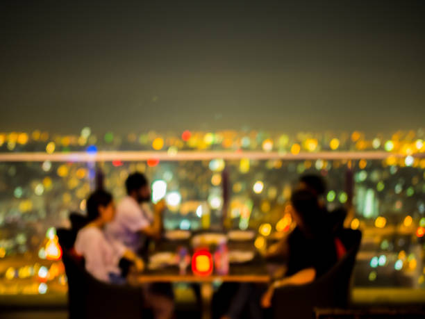 Blurred focus of rooftop restaurant with people dinning at night stock photo