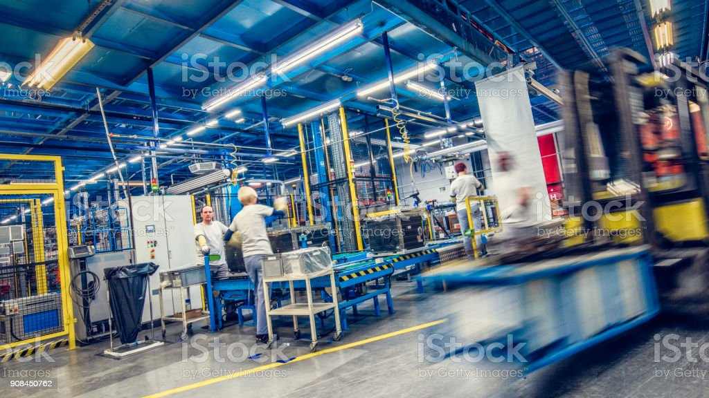 Blurred forklift and factory workers stock photo