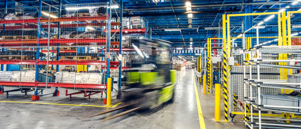 blurred forklift in factory - metal robot in logistic factory foto e immagini stock