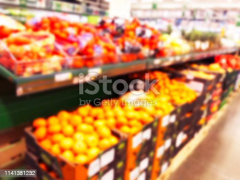 823709528 istock photo Blurred fresh fruits and vegetables at retail store. Abstract background of supermarket. Grocery market blurred background. Fruits in store racks. Interior shopping mall defocused background 1141381232
