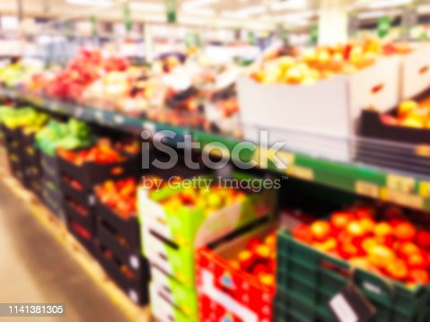 823709528 istock photo Blurred fresh fruits and vegetables at retail store. Abstract background of supermarket. Grocery market blurred background. Fruits in store racks. Interior shopping mall defocused background 1141381305