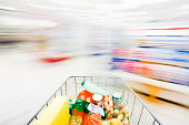 A filled shopping cart streaks towards a junction in a ghostlike supermarket's aisles which are blurred beyond recognition by the speed the cart is moving.
