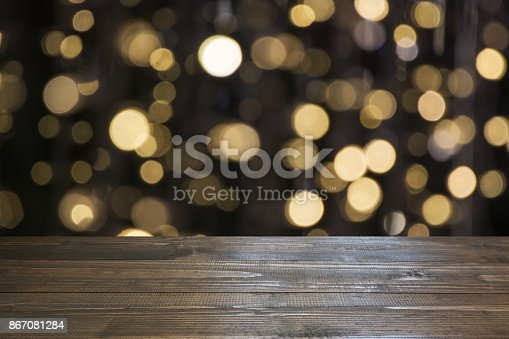 istock Blurred gold garland and wooden tabletop as foreground. Image for display or montage your christmas products. 867081284