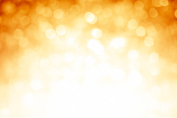 blurred gold sparkles background with darker top corners - high key stock pictures, royalty-free photos & images