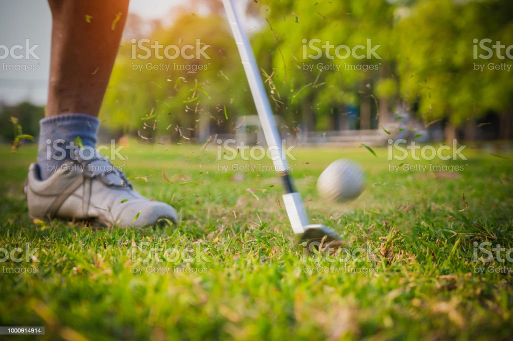 Blurred golf club and golf ball close up in grass field with sunset....