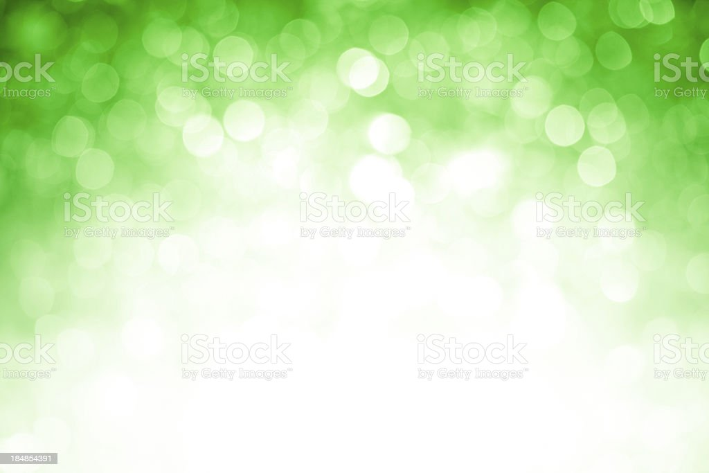 Blurred green sparkles background with darker top corners, bright center stock photo