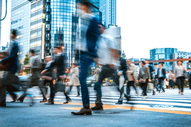 日本の路上で通勤するビジネスマンのぼやけたグループ - 雑踏 ストックフォトと画像