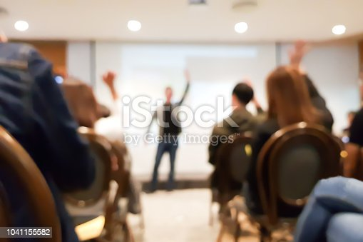 istock blurred group of people meeting in motivation seminar event at convention hall, speaker raising hand up and audience action follow , cheerful concept 1041155582