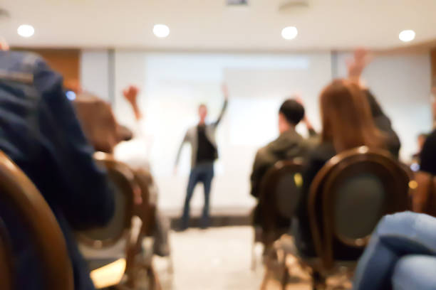 blurred group of people meeting in motivation seminar event at convention hall, speaker raising hand up and audience action follow , cheerful concept stock photo
