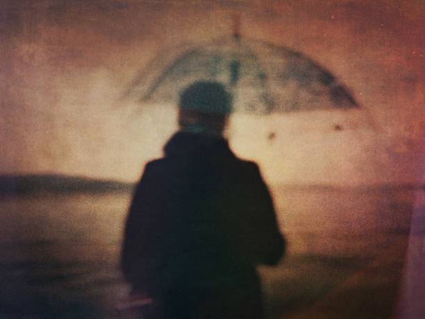 Blurred grunge view of a woman with umbrella on the seaside