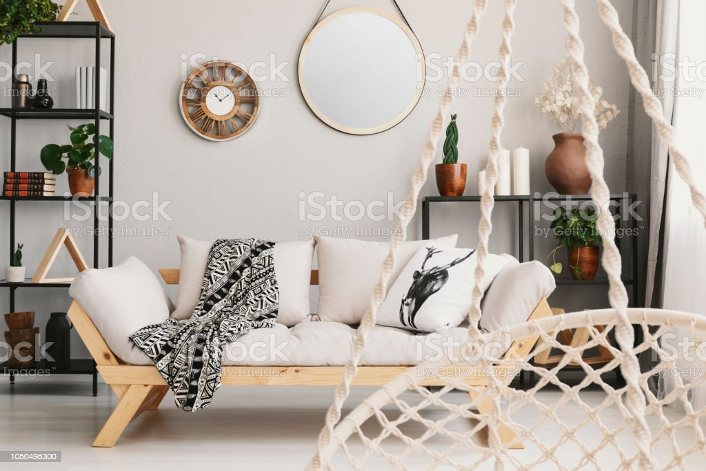 Blurred Hanging Chair In The Foreground And Wooden Sofa In Living Room  Interior With Mirror Real Photo Stock Photo - Download Image Now