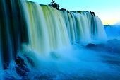 Impressive Iguacu falls at gold colored sunset with rainbow, one of the most beautiful waterfalls in the world and one of the seven Wonders of Nature, dramatic beauty in nature landscape - Idyllic Devil's Throat - international border of Brazilian Foz do Iguacu city, Parana State, Argentina Puerto Iguazu city, Misiones province and Paraguay - rainforest landscape panorama, South America
