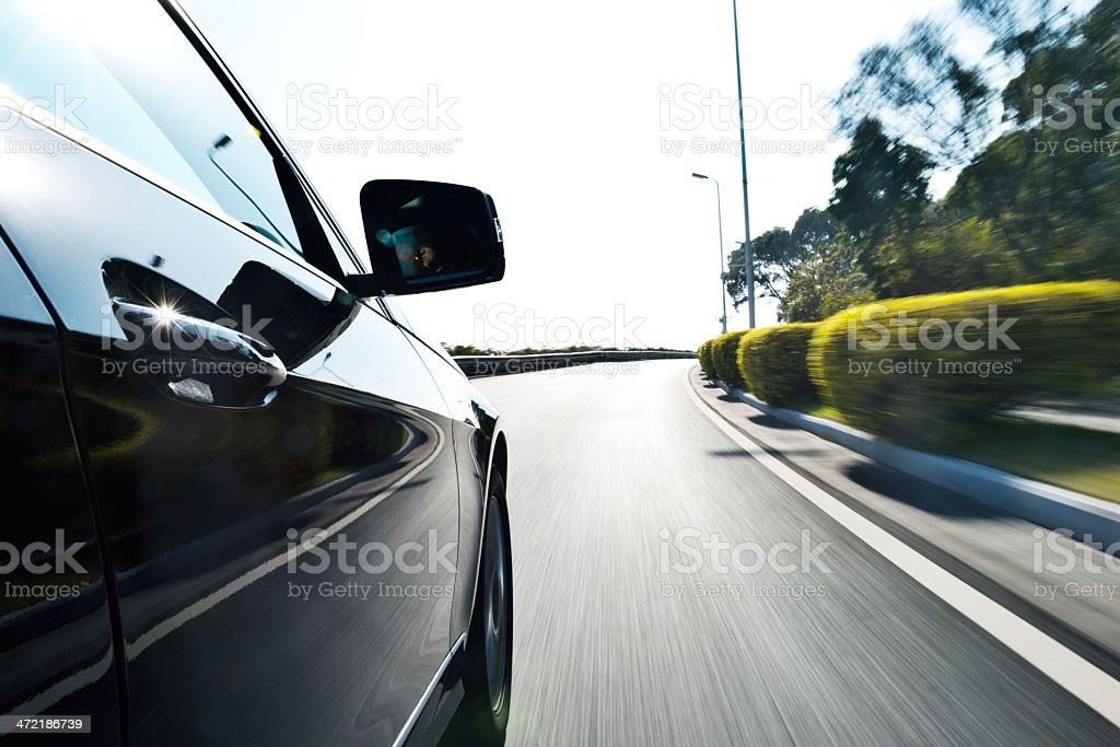 Blurred image of a black car driving along a road with hedge stock photo