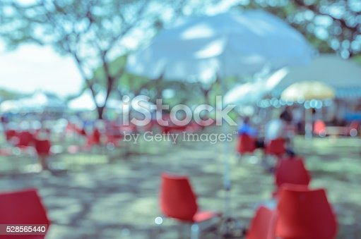 Blurred image of a fair in green park. Abstract background for festival and market. Vintage filtered effect image