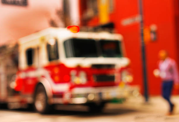 blurred image of a fire engine on a city street - emergency response stock pictures, royalty-free photos & images