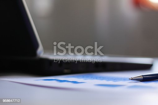 879125330 istock photo blurred image of a notebook and a pen on the desktop.business background 958647712